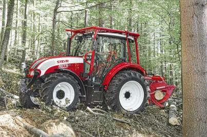 Červený traktor STEYR při práci v lese